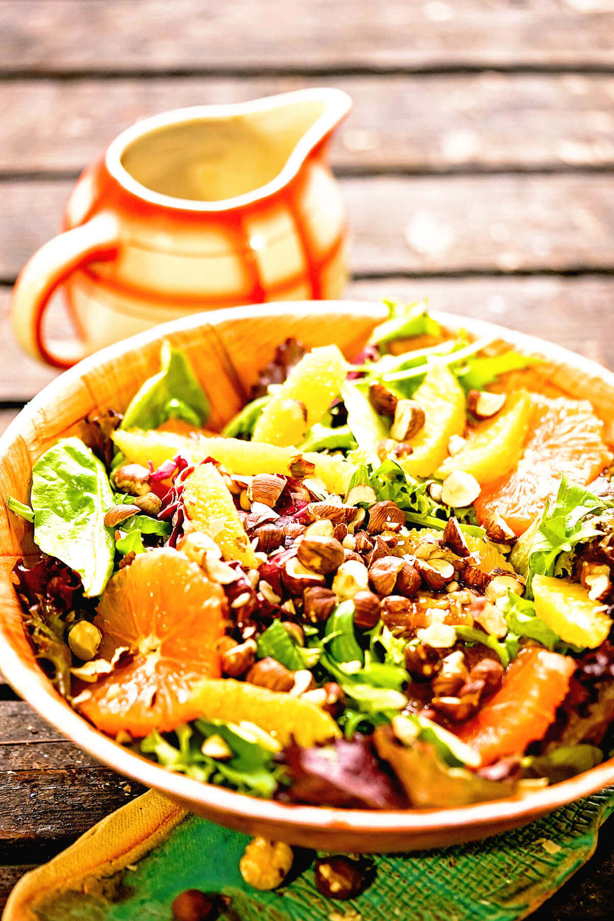 Citrus Salad Recipe in wooden bowl with salad dressing on the side.