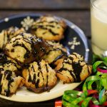 Coconut Macaroons with chocolate drizzle on plate with a glass of milk.