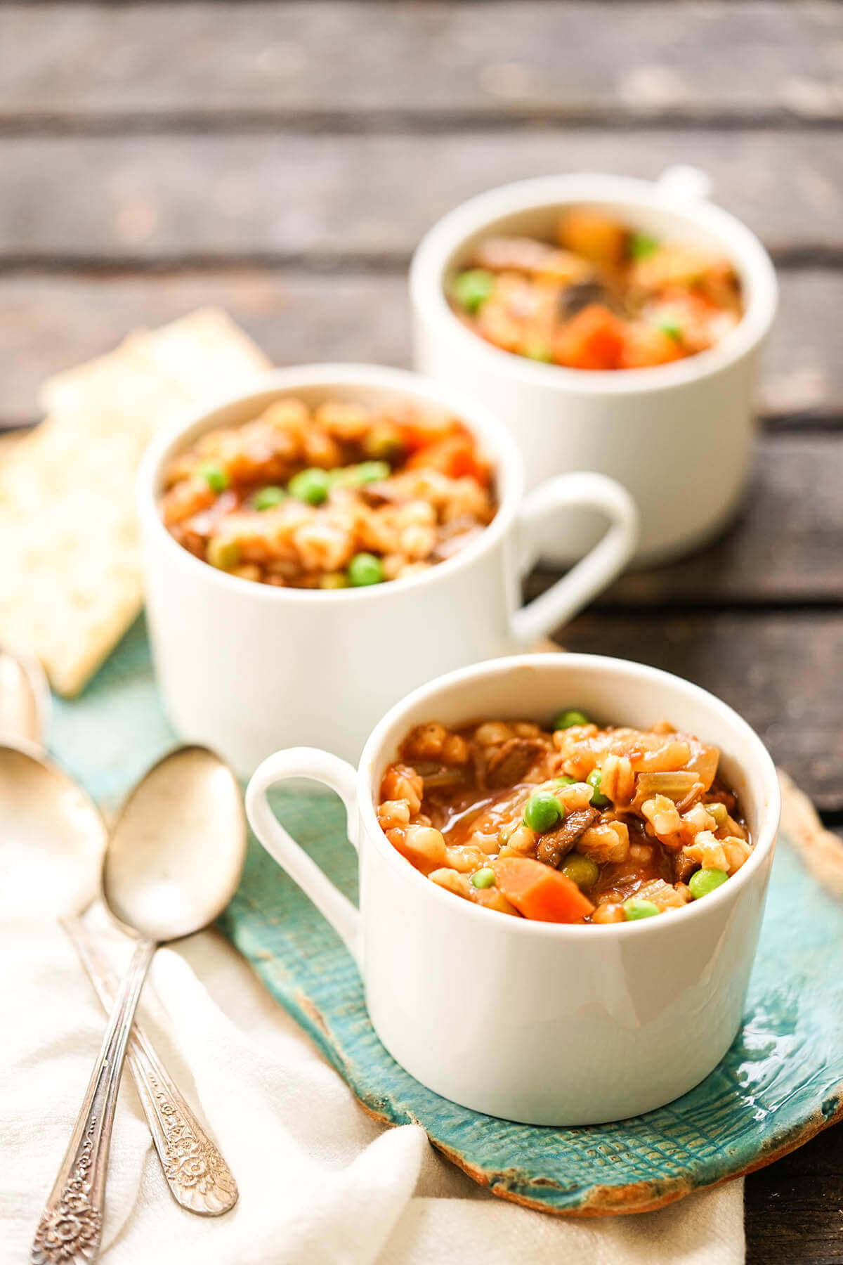 Beef Barley Soup in white bowls with spoon.