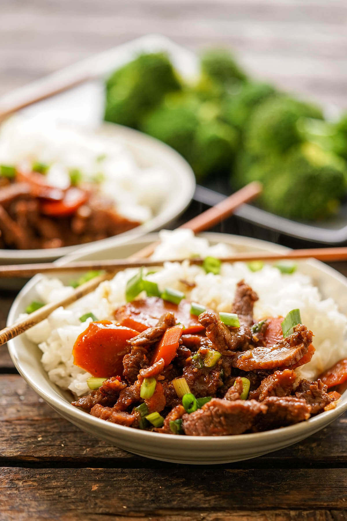 Pressure Cooker Mongolian Beef in bowls with white rice and chopsticks.