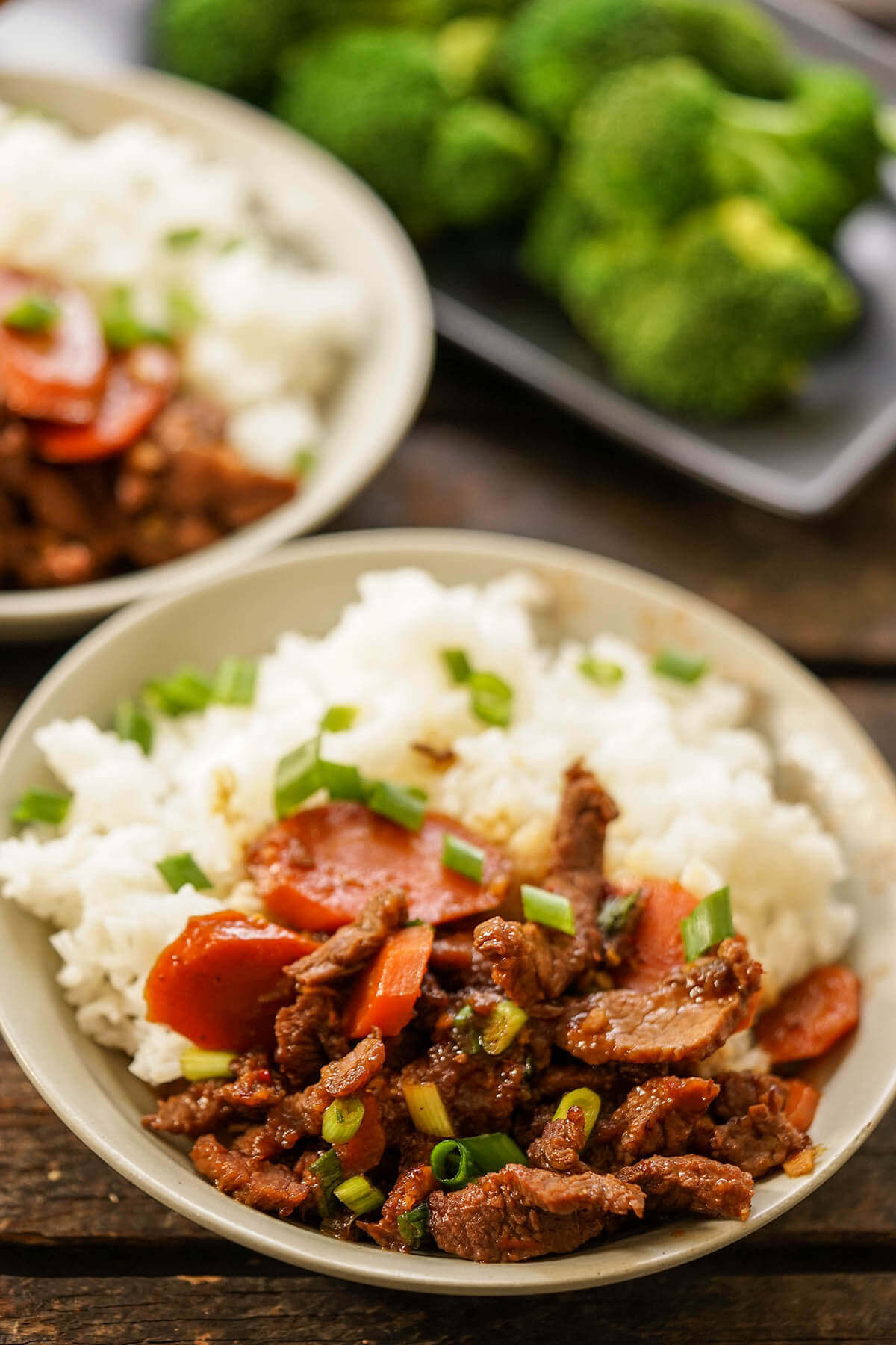 Mongolian Beef in gray bowl served with white rice and broccoli.