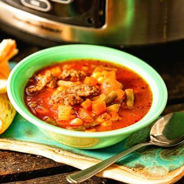 Vegetable beef stew in green bowl with spoon.