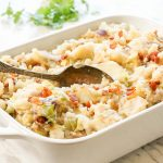 Colcannon in white dish topped with crispy bacon with spoon