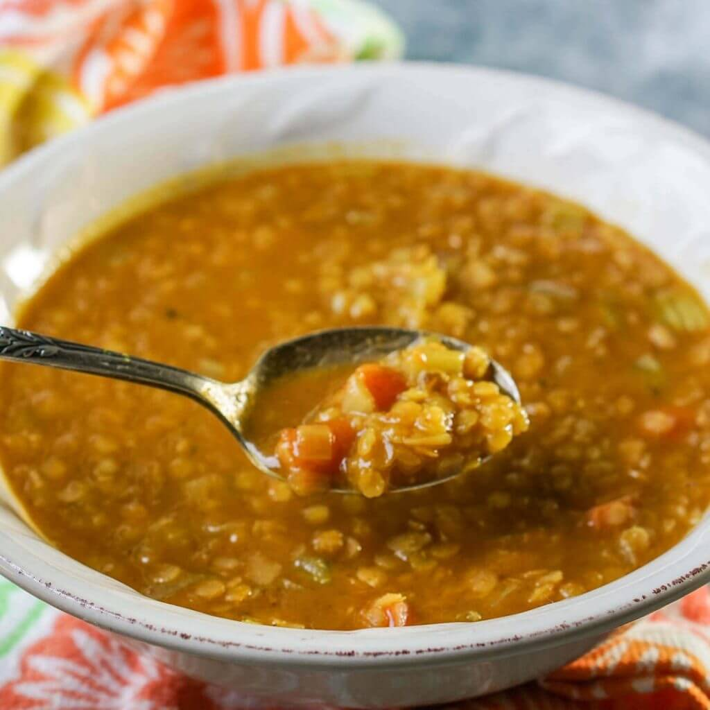 Golden Lentil Soup in white bowl with spoon.