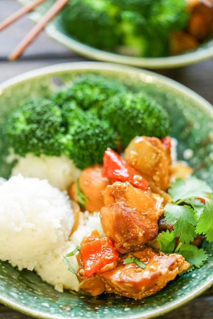 Asian Chicken in rice bowl served with steamed broccoli.