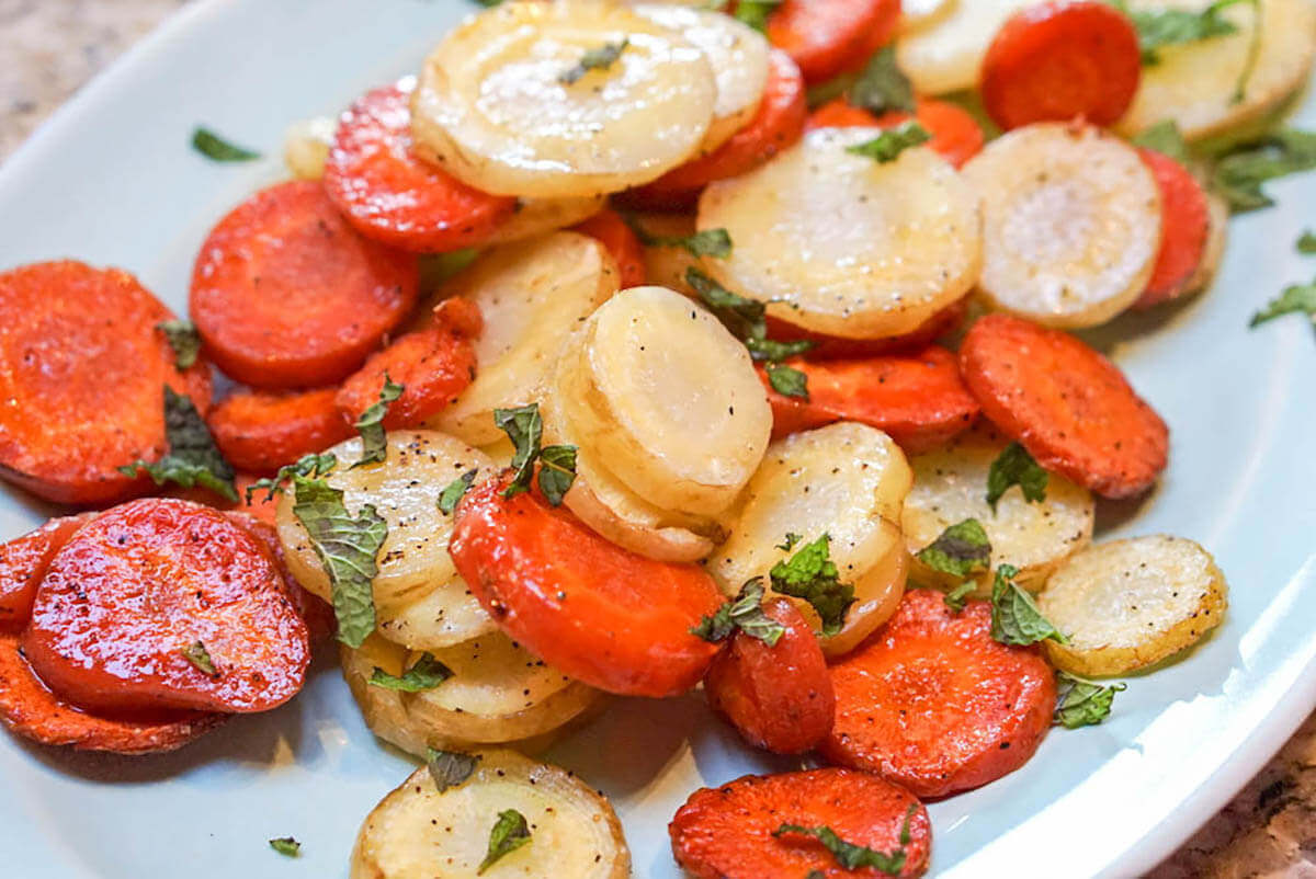 Roasted Carrots on white plate sprinkled with mint.