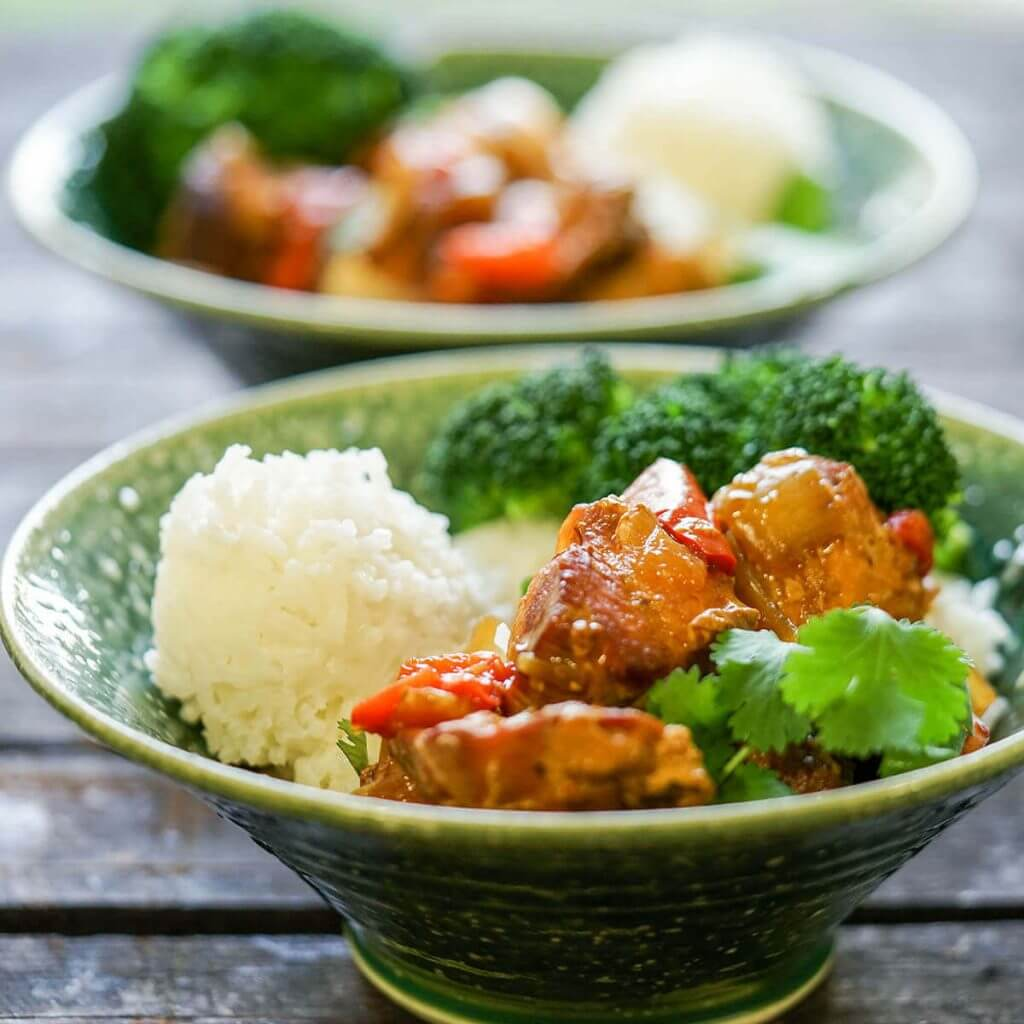Green bowls filled with Sriracha Chicken and Rice.