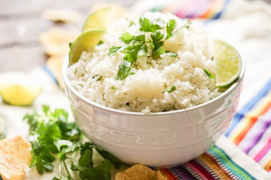 Rice in white bowl surrounded by chips.