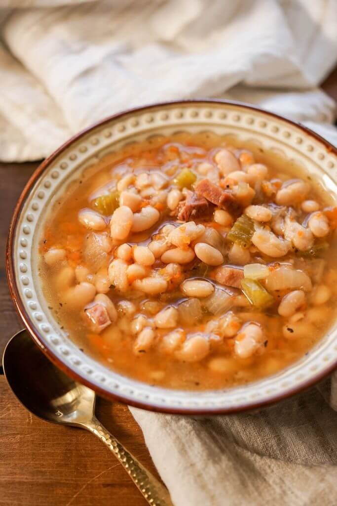 Ham and Bean Soup in white bowl with spoon on napkin.