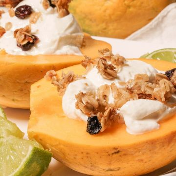 Golden papaya breakfast bowl topped with thick greek yogurt, crunchy granola surround by wedges of lime.