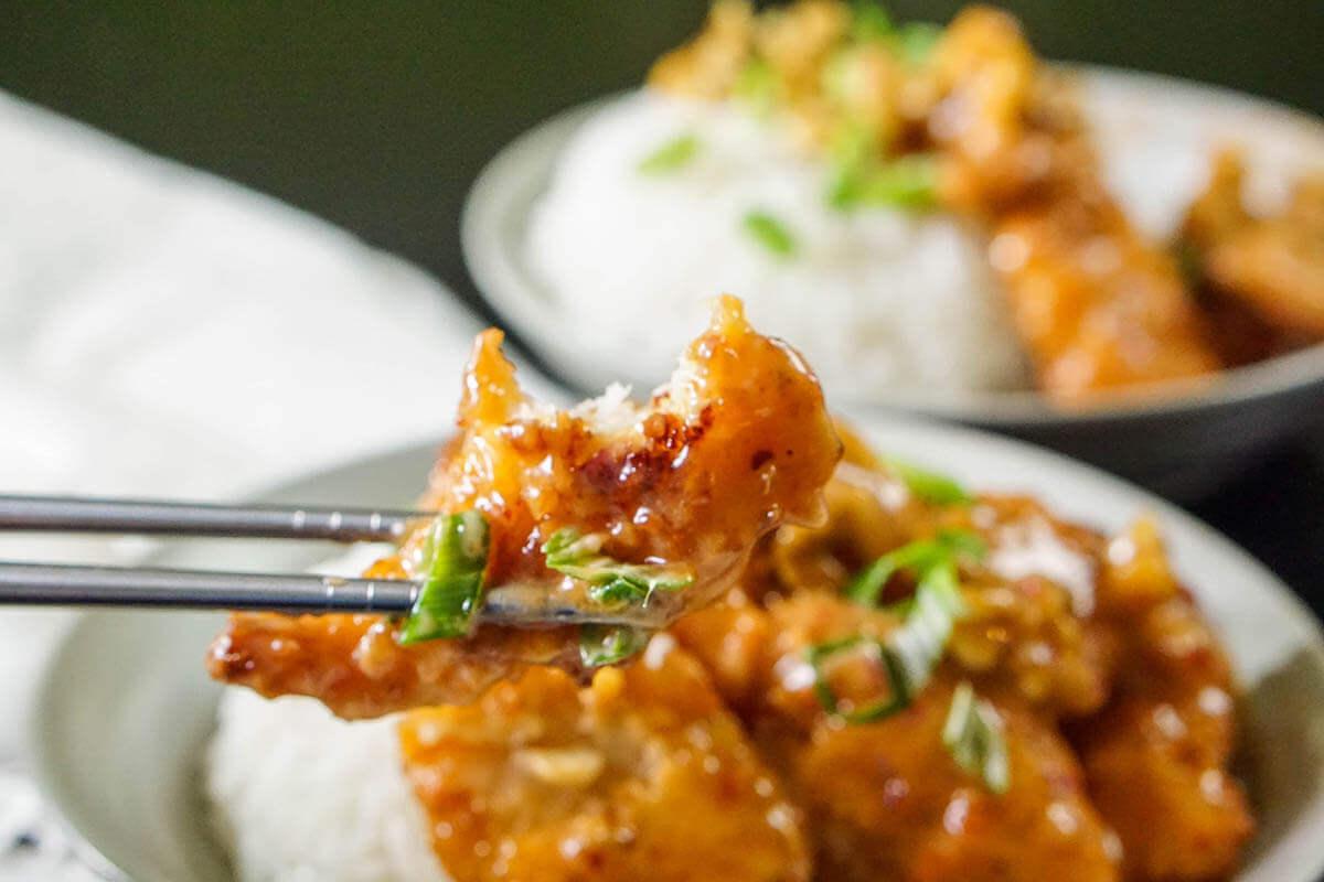 Chopsticks holding cooked shrimp.