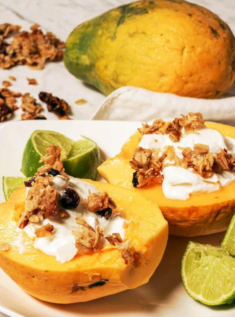 Papaya breakfast bowl filled with yogurt, topped with granola