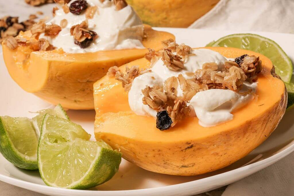 Papaya Breakfast Bowl topped with yogurt and lime.