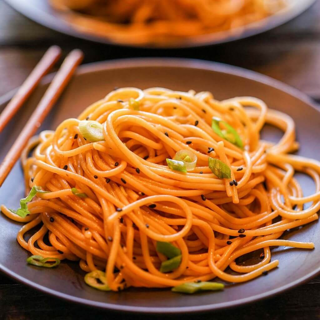 Spicy Sesame Noodles on black plate with chopsticks