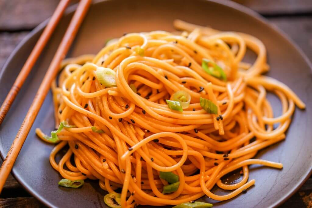 Asian noodles topped with a fiery sauce on a black plate served with chopsticks.