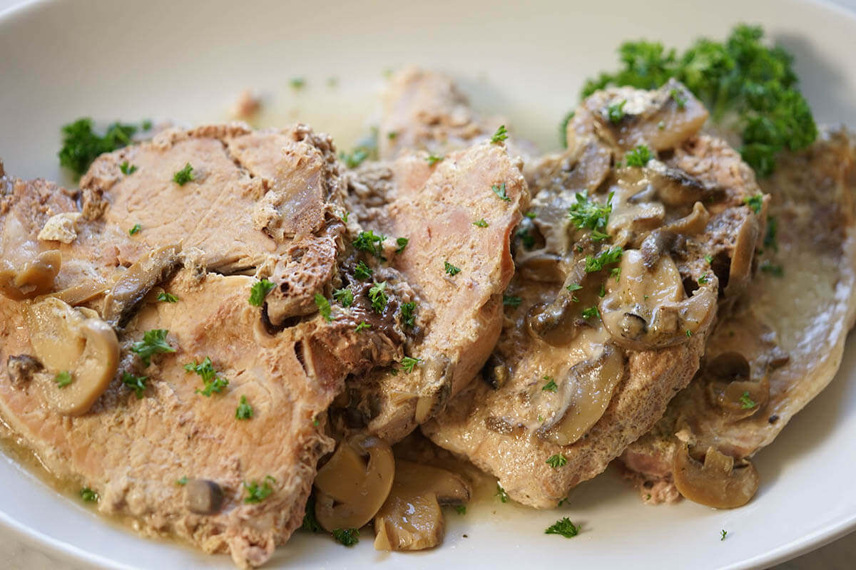 Meat on a white platter topped with gravy and sprinkles with minced parsley.