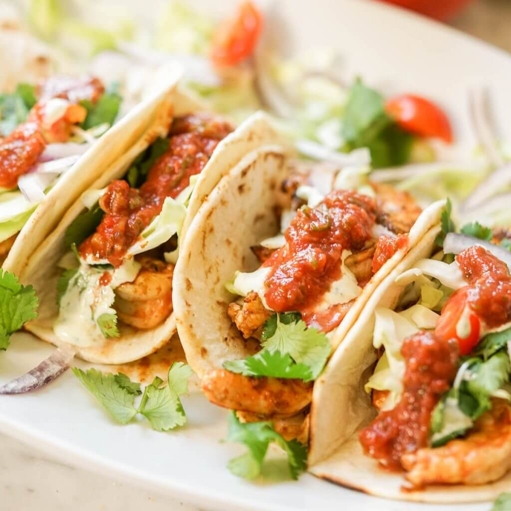Shrimp tacos topped with cabbage, tomatoes and cilantro on white platter