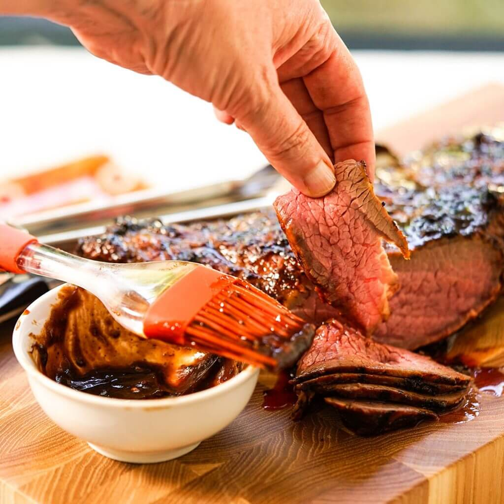 Hand grabbing a piece of sliced beef steak on cutting board slathered with bbq sauce