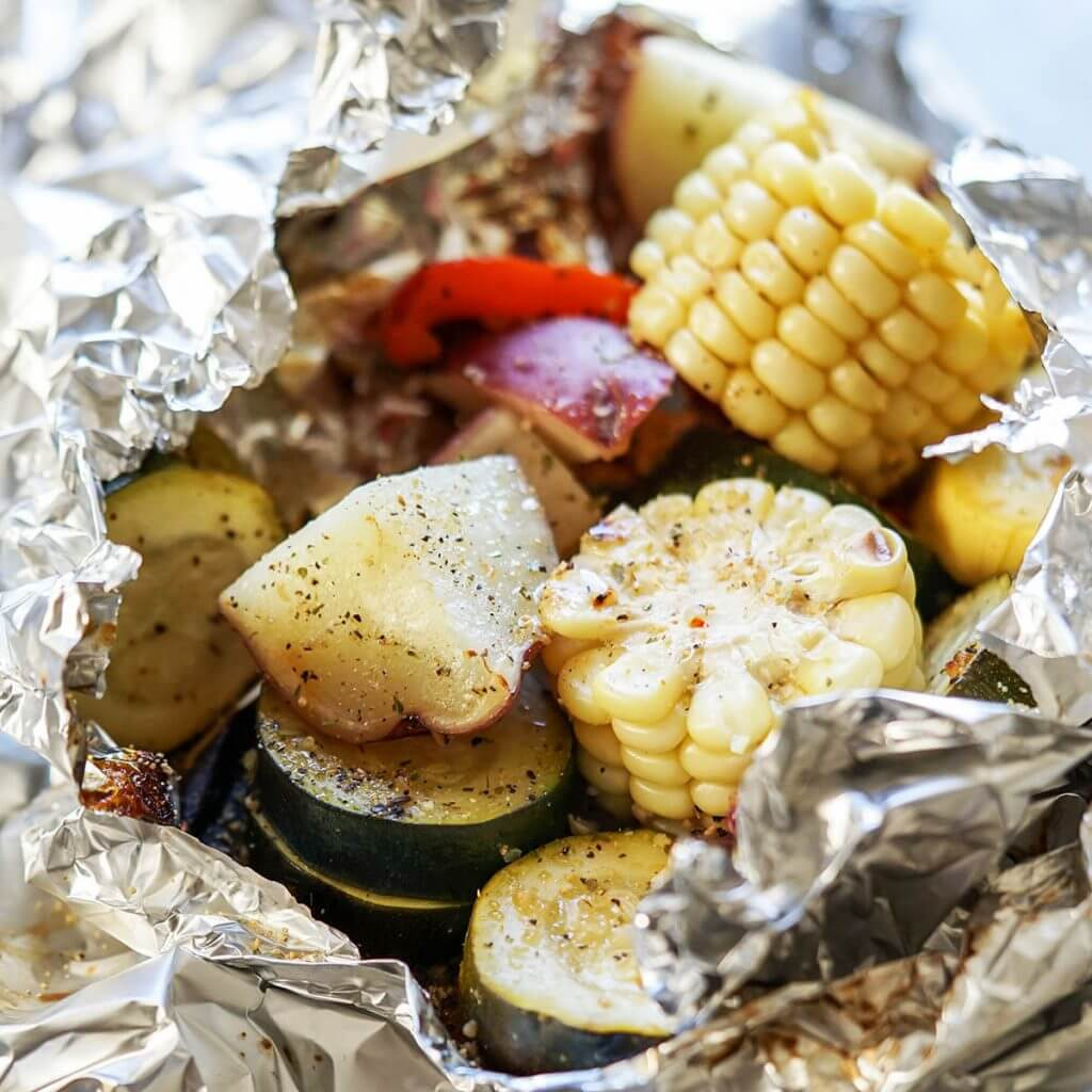 Grilled vegetables in foil packet - corn, potatoes, zucchini and onions.