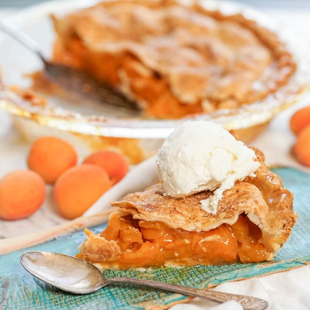 Homemade Apricot Pie Recipe on blue plate with vanilla ice cream .