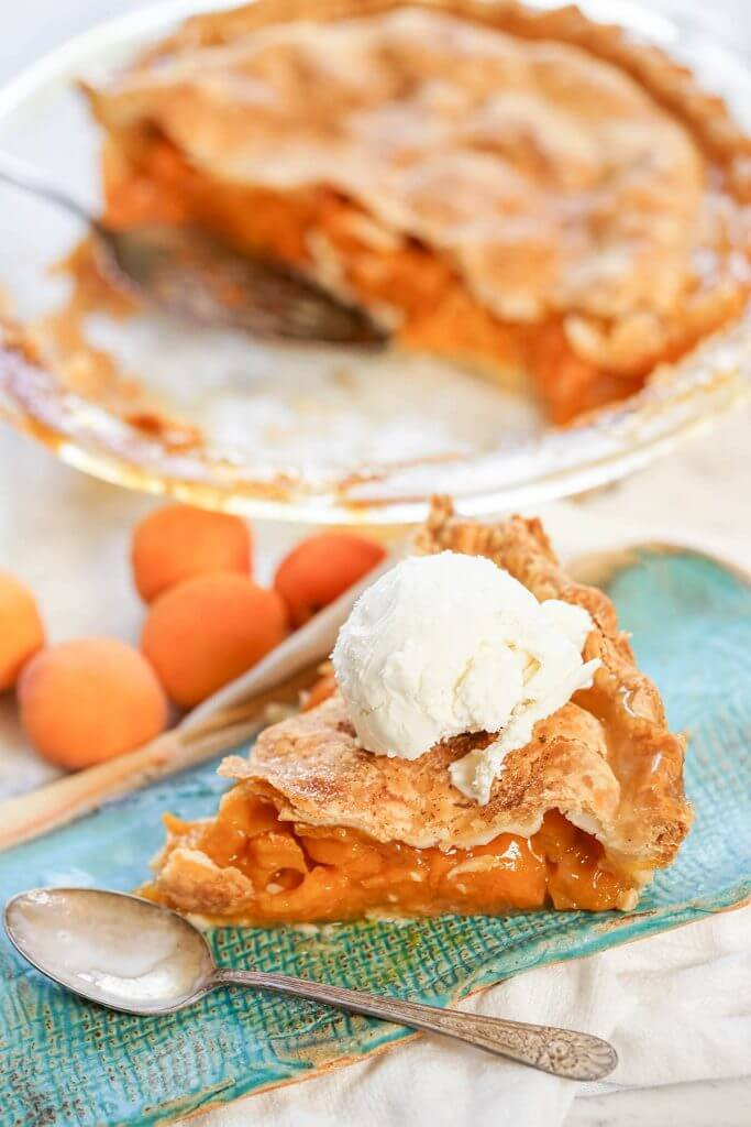 Sliced Pie on plate with spoon. Pie is topped with a scoop of ice cream.