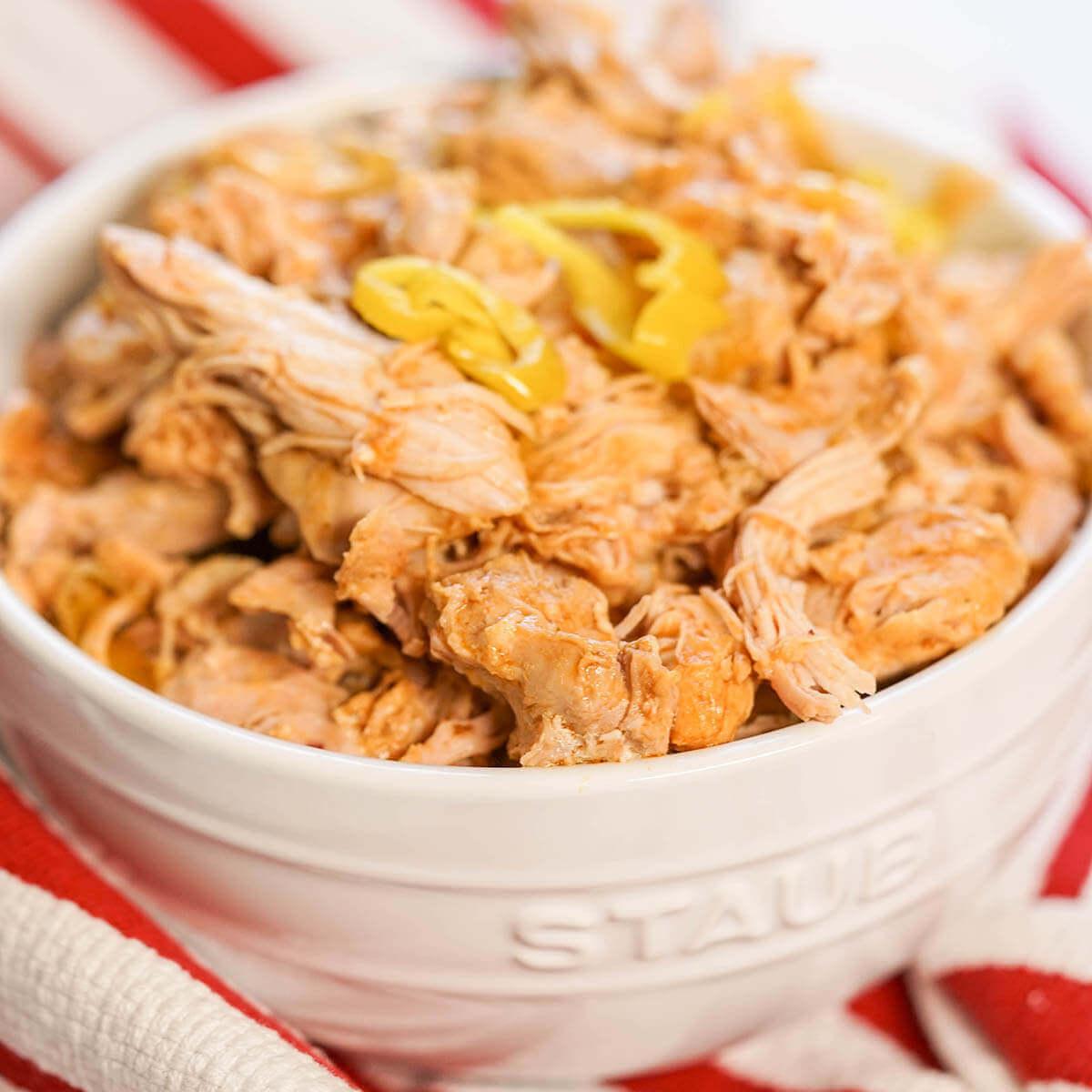 Shredded chicken in white bowl.
