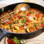 Ground Chicken and Zucchini casserole in cast iron skillet with spoon.