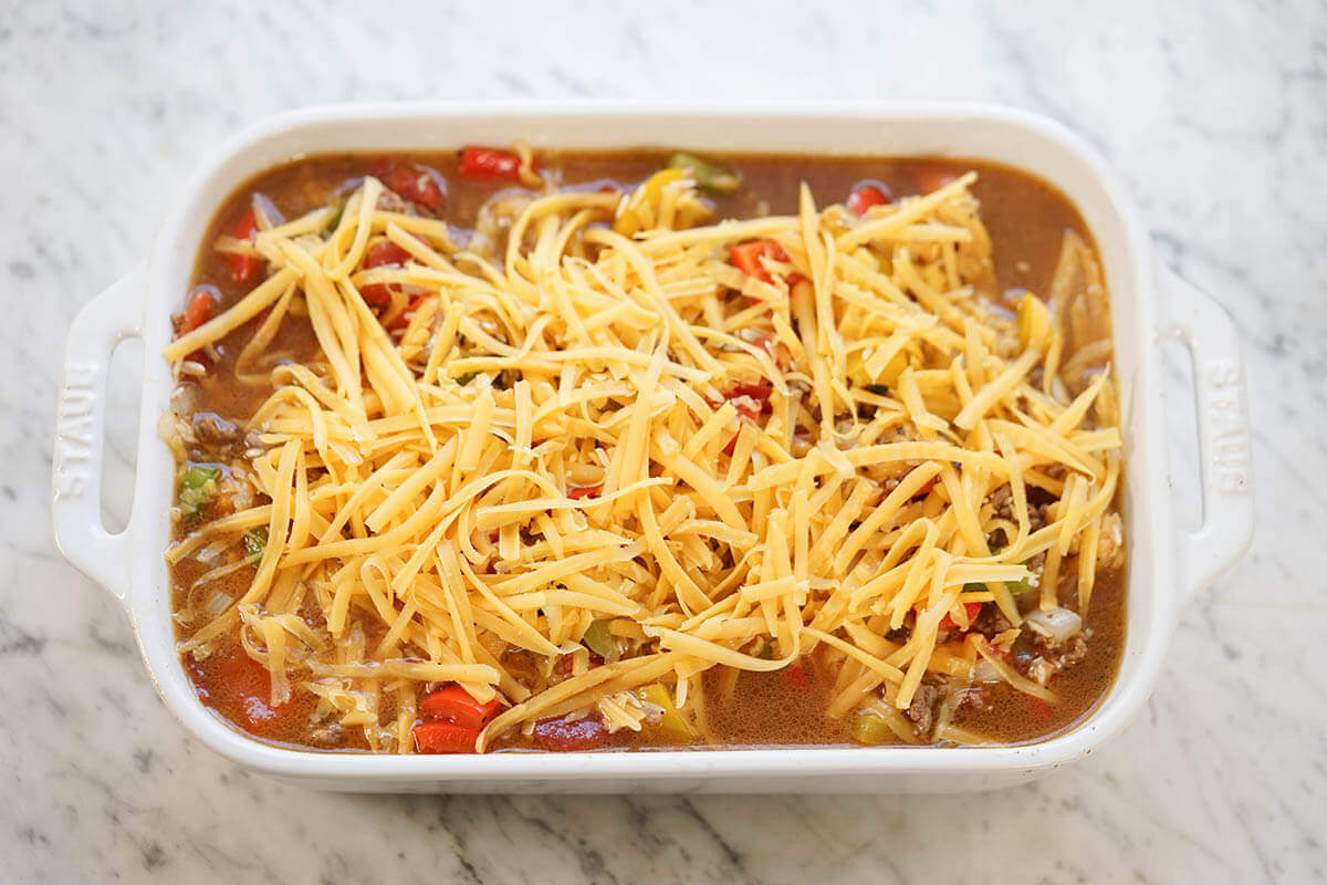 Pan with assembled ingredients topped with shredded cheese, ready to bake.