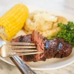 Tenderloin steak on plate with potatoes and corn.
