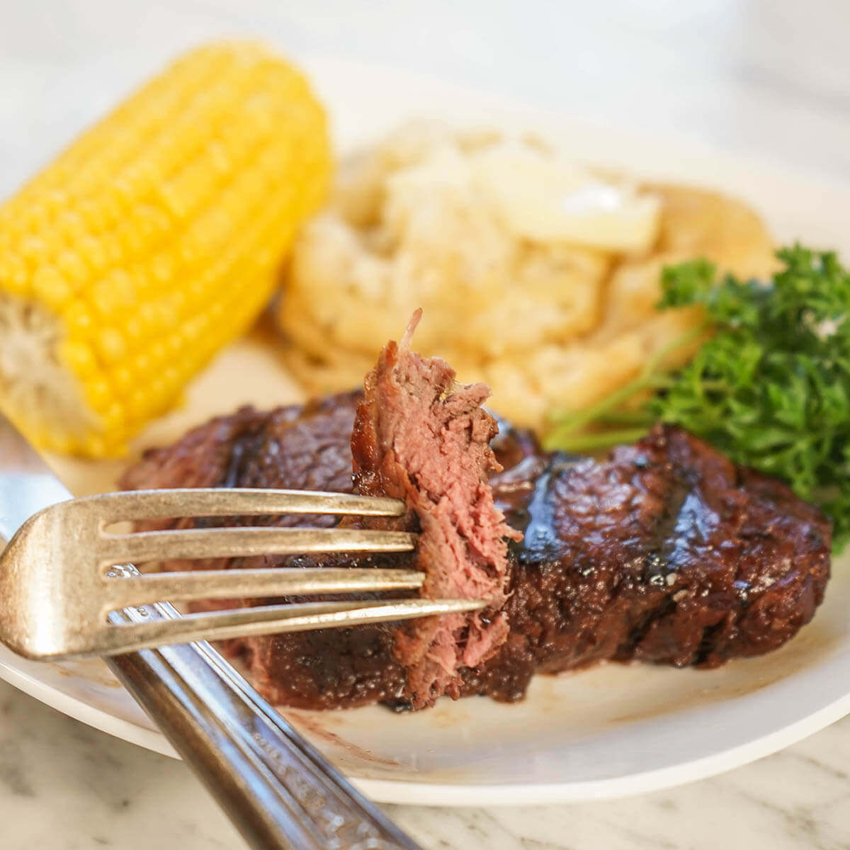 Tenderloin steak on plate with potatoes and corn.