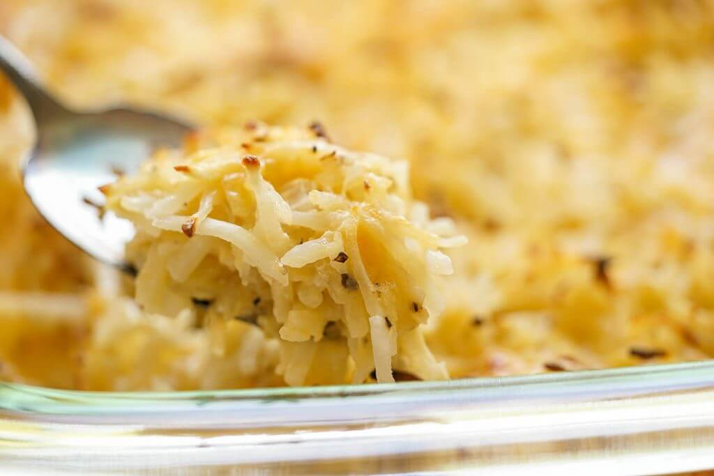 Casserole filled with Cracker Barrel Cheesy Potatoes being dished up with spoon.
