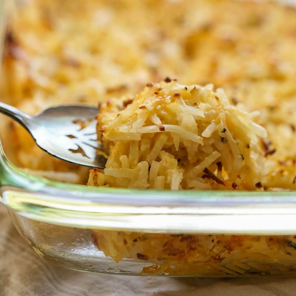 Casserole dish filled with Cracker Barrel Cheesy Potatoes being serve with a spoon.