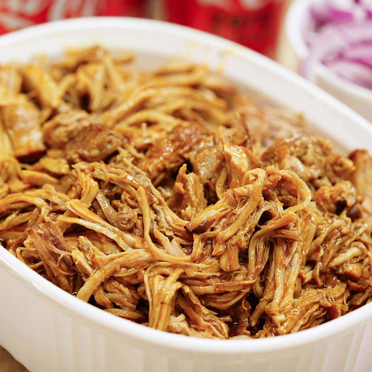BBQ pulled pork that has been shredded in white bowl.