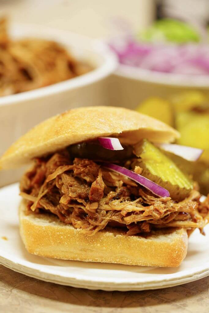 Shredded Pork Sandwich topped with a pickle and red onion.