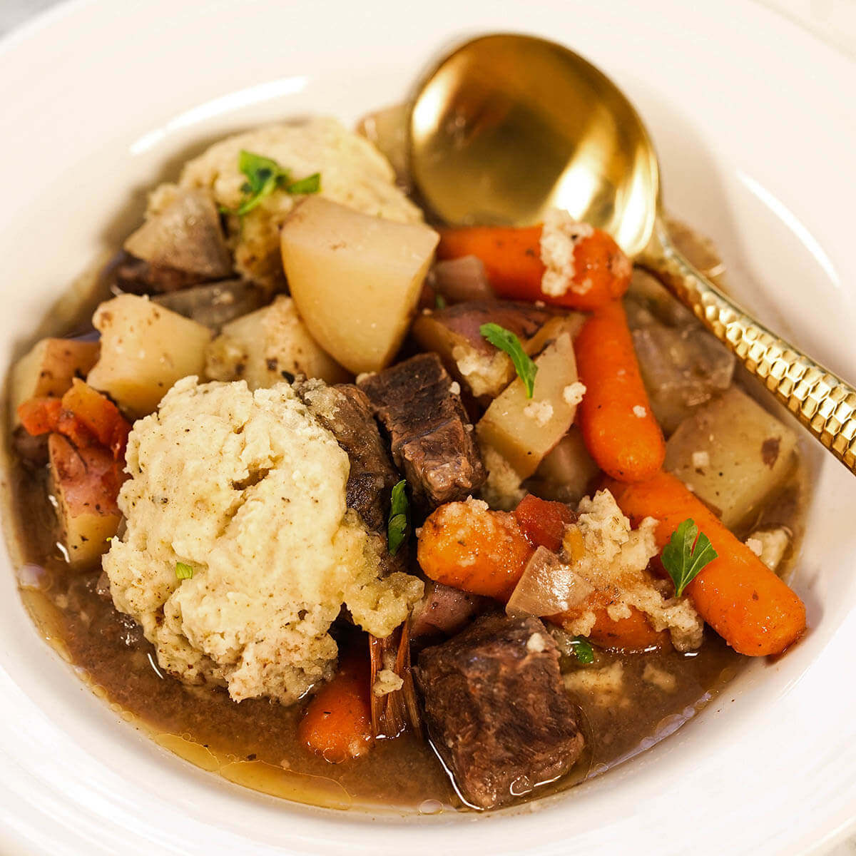 Beef Stew with dumplings in a white bowl.