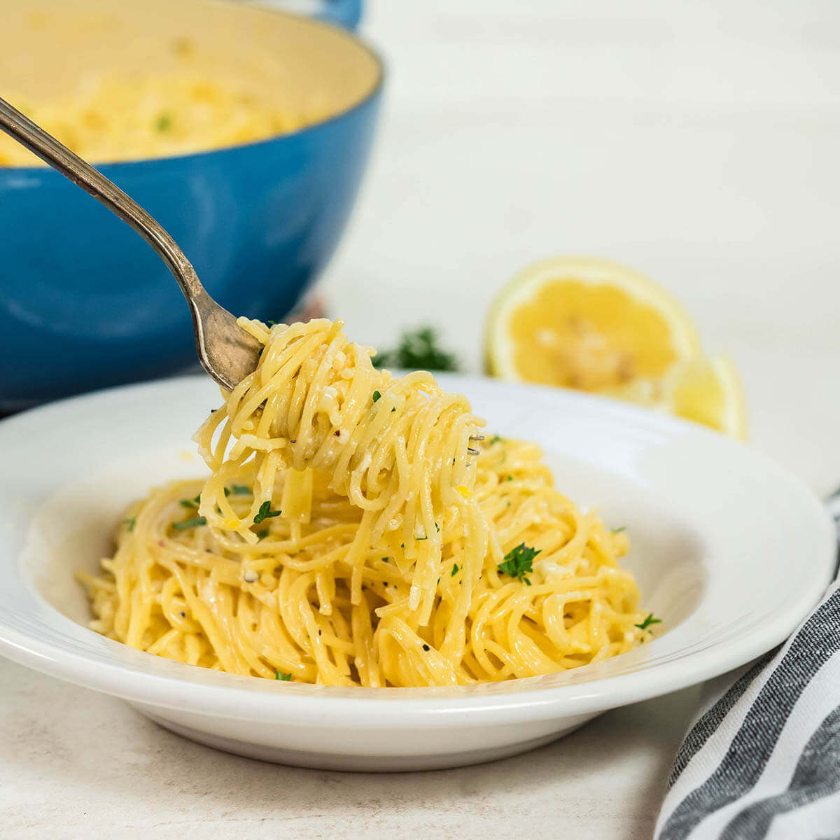 A big helping of pasta served in a white dish. A fork is twirled around a generous bite!