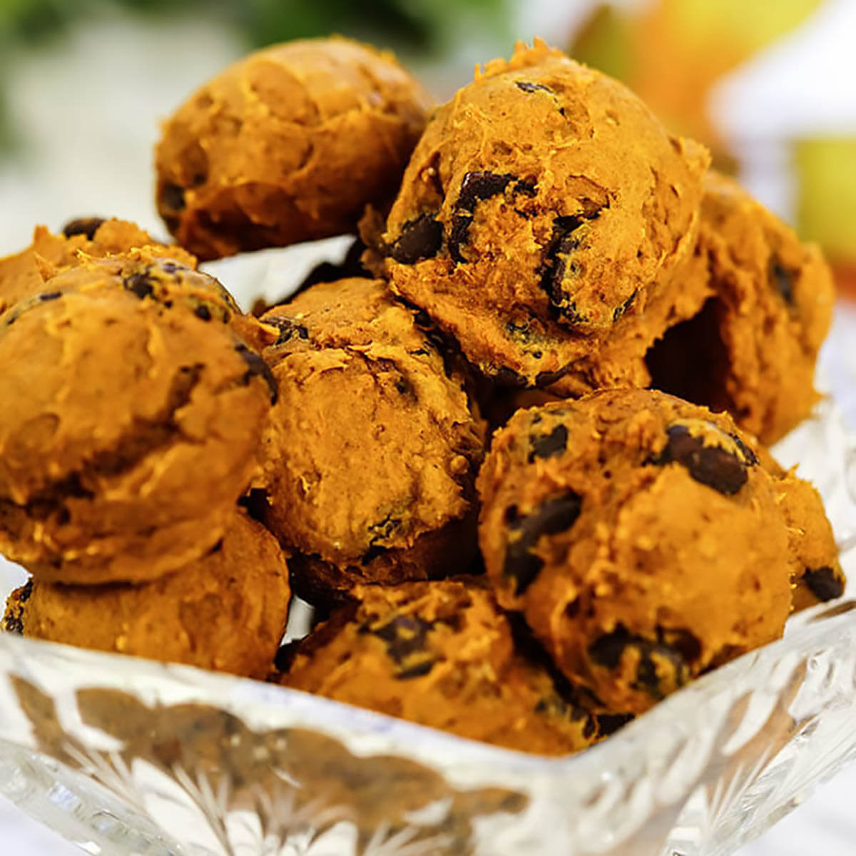 A big pile of pumpkin chocolate chip cookies on glass plate.