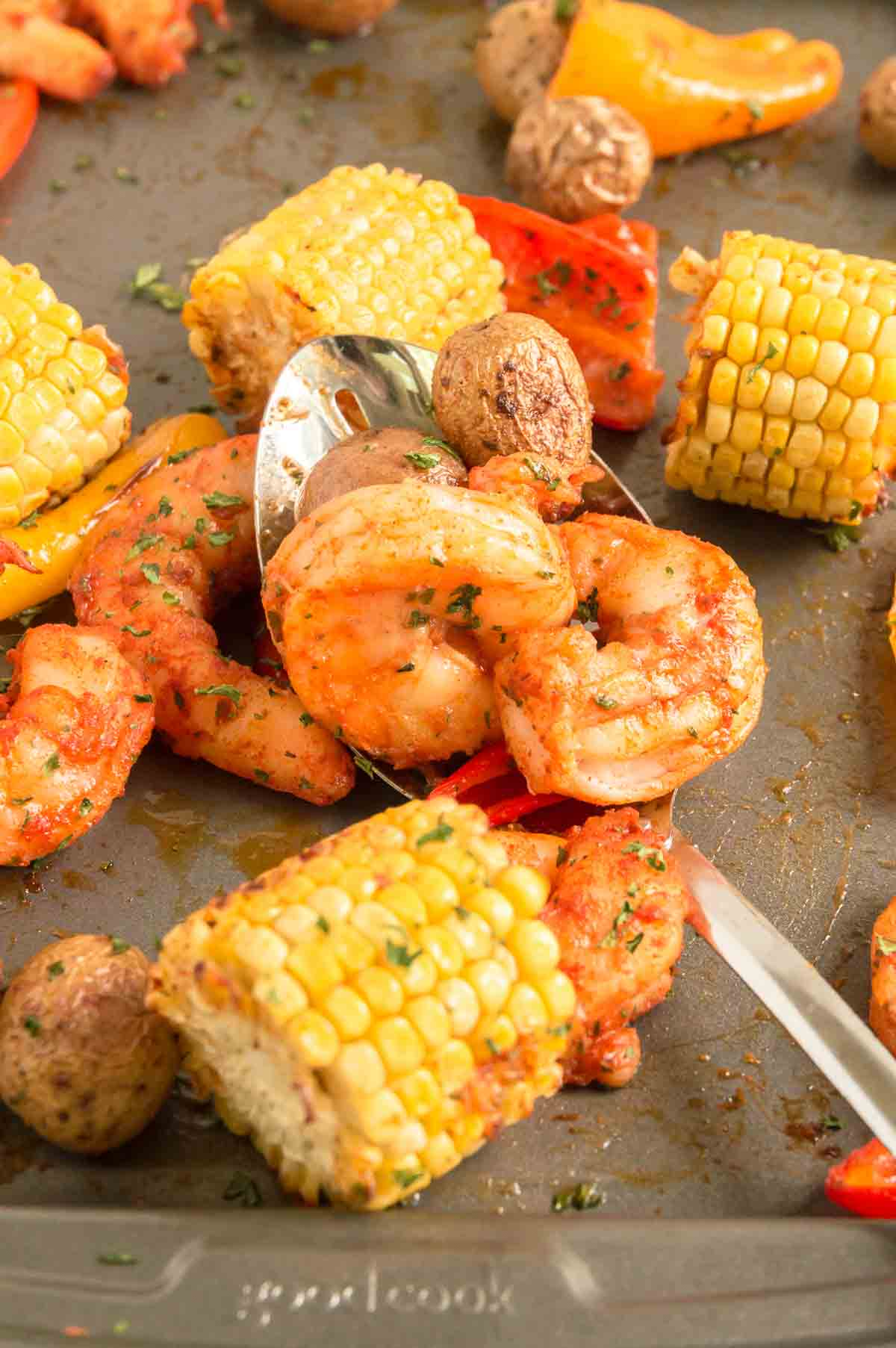 sheet pan filled with roasted corn, potatoes and shrimp