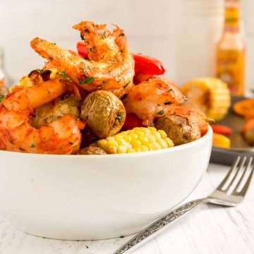 Cajun shrimp with potatoes and carrots served in a white bowl.