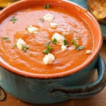 Homemade Tomato Bisque soup garnished with chunks of goat cheese and ribbons of basil.