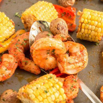 Cajun Sheet Pan Shrimp with corn, peppers and shrimp with spoon.