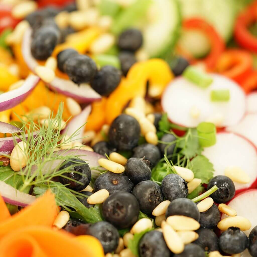 A garden salad filled with fresh veggies and blueberries.