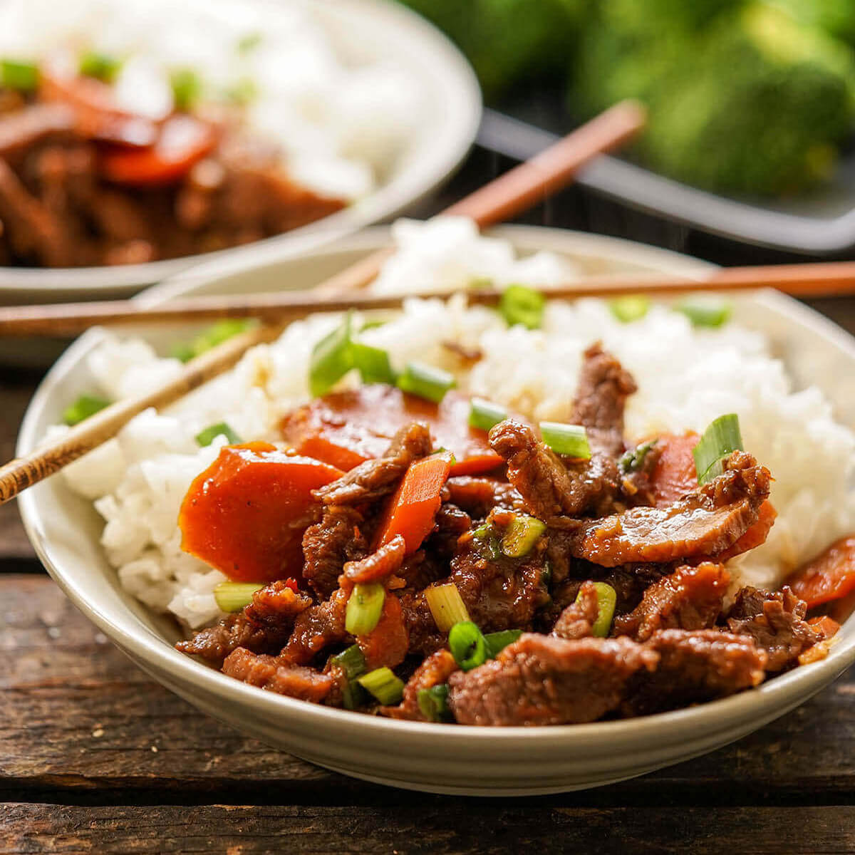 Mongolian Beef served over rice with chopsticks.