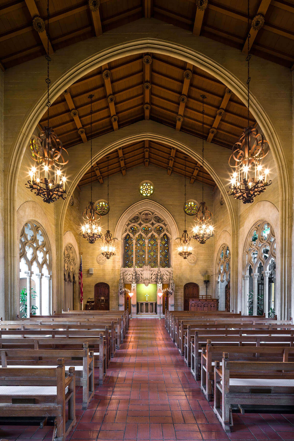 A glimpse down the aisle into a beautiful chapel adorned with chandeliers and stained glass windows.