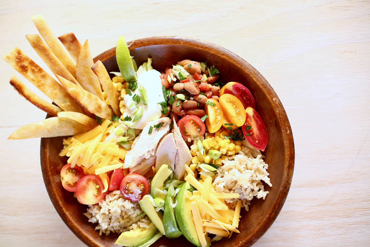 Rotisserie Chicken Burrito Bowl with lettuce, avocado, tomatoes and tortilla strips.