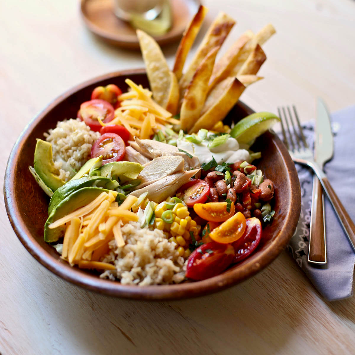 Big salad with lettuce, rice, chicken, cheese and tortilla strips in bowl.