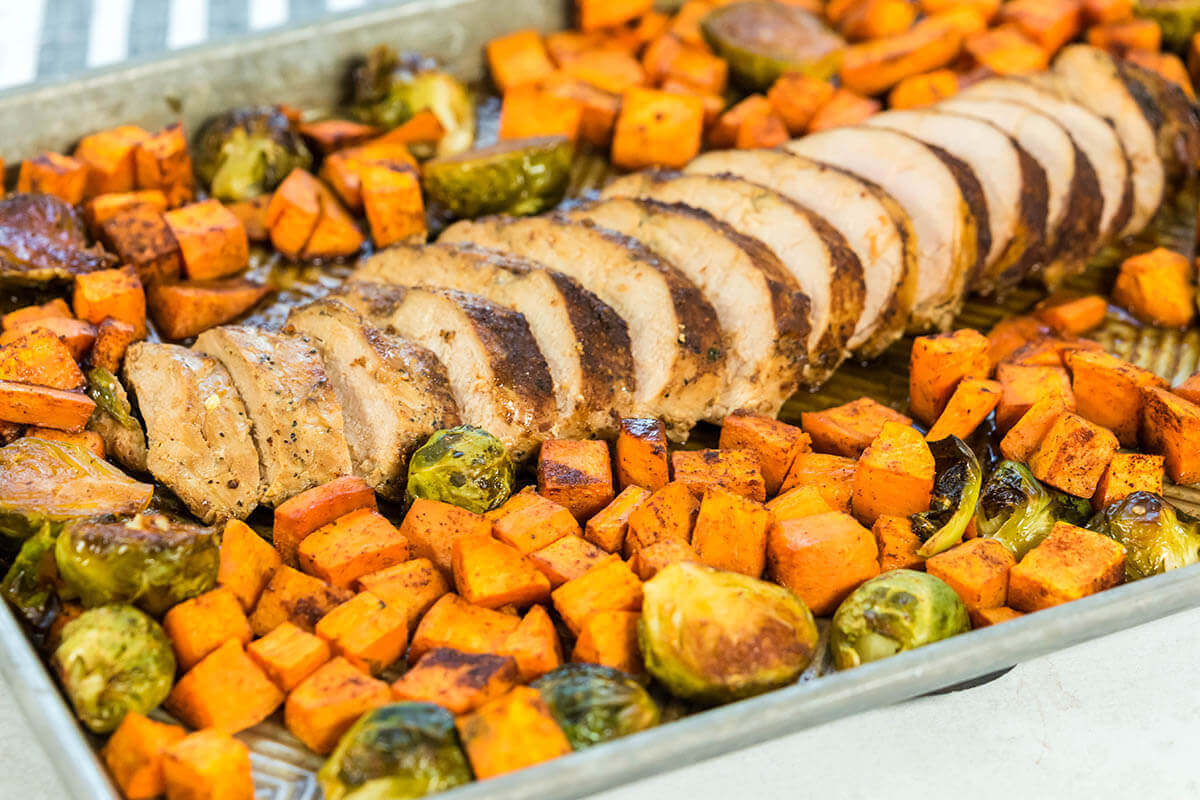 Sliced pork tenderloin and sweet potatoes on sheet pan ready to serve.