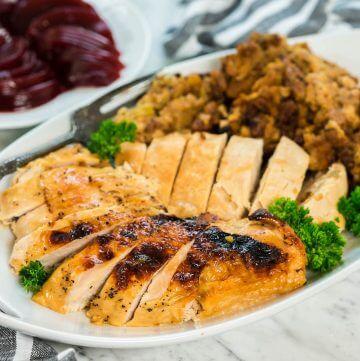 A platter filled with Crockpot Stuffed Turkey Breast.