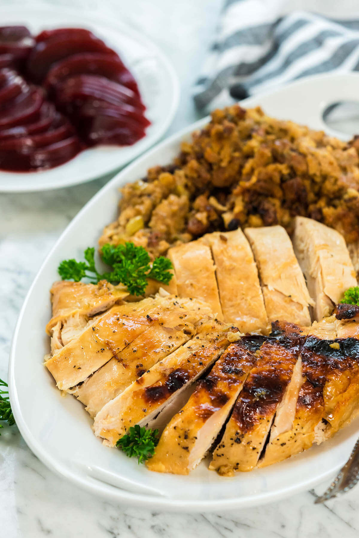 A platter filled with sliced turkey breast and stuffing.