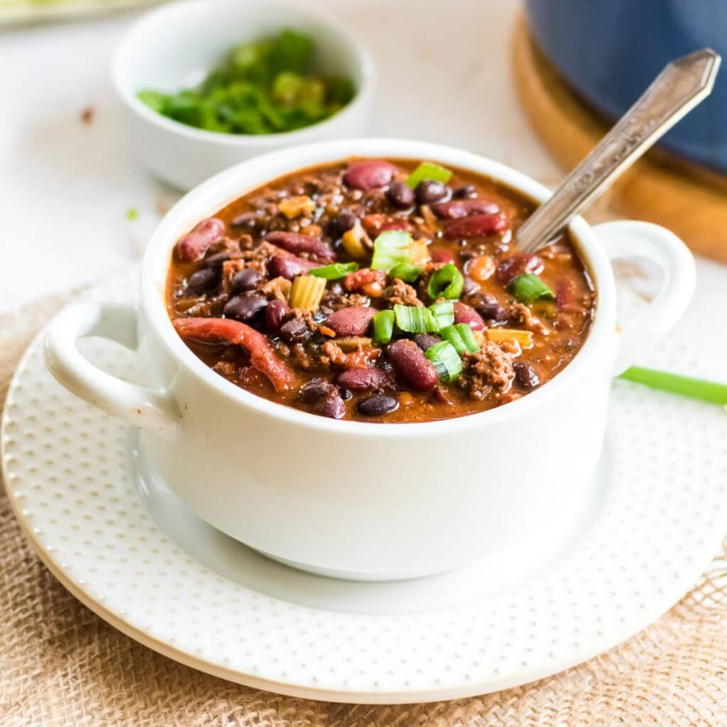 Closeup of chili in a white bowl with a spoon, ready to be enjoyed.